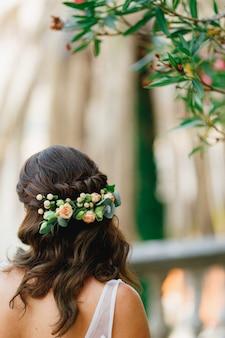 Una sposa con un ornamento di fiori naturali tra i capelli si trova sotto una vista posteriore di un oleandro in fiore