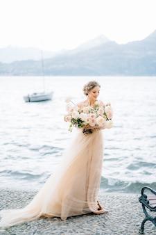La sposa con un mazzo di fiori si trova sulla riva del lago di como sullo sfondo di yacht e