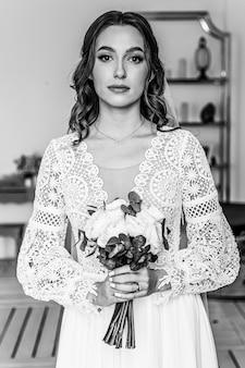 La sposa con un bouquet di fiori freschi in un bellissimo abito festivo con pizzo.
