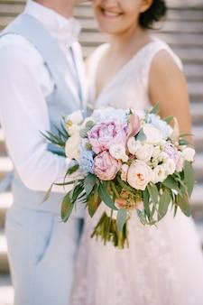 La sposa con il mazzo di rose e peonie e lo sposo stanno abbracciati sulle antiche scale in