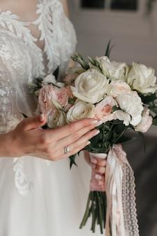 Sposa con bouquet, rosa bianca, manicure, abito bianco