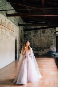 Sposa con una candela in mano cammina lungo una loggia in un'antica villa