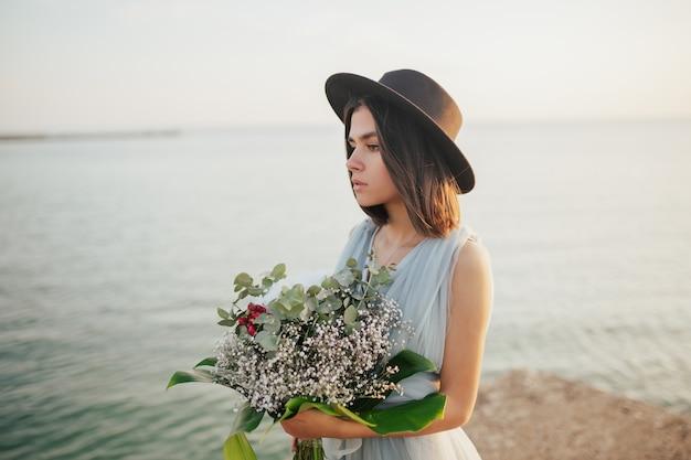 Sposa con cappello in piedi vicino al mare con bellissimo bouquet da sposa