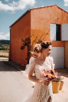 Una sposa dai lineamenti piacevoli in un abito da sposa con un bouquet creativo.