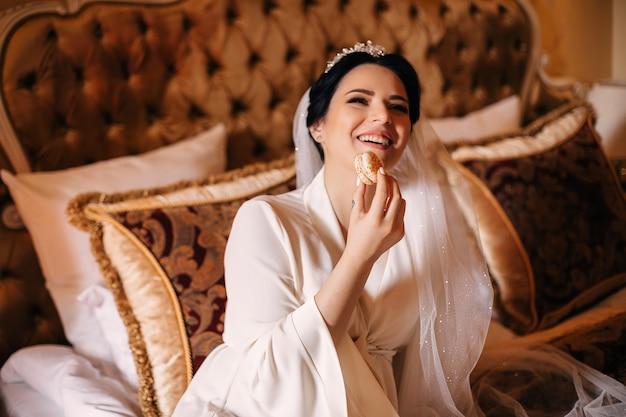 La sposa con velo da sposa e veste bianca si siede sul letto e mangia amaretto. sorriso sincero della sposa.
