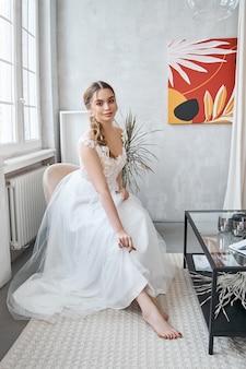 Donna sposa in un abito da sposa estivo leggero seduto alla finestra e in attesa della cerimonia nuziale