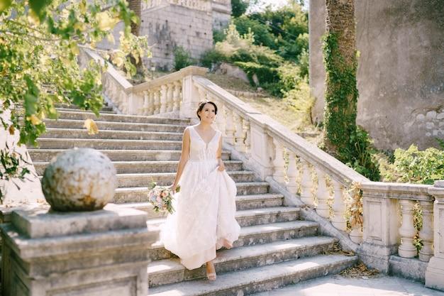 La sposa in ghirlanda scende le scale pittoresche dell'antico tempio di prcanj vista posteriore