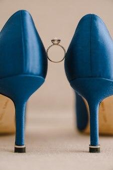 Anello di fidanzamento delle spose con gemma tra le scarpe blu a tacco alto