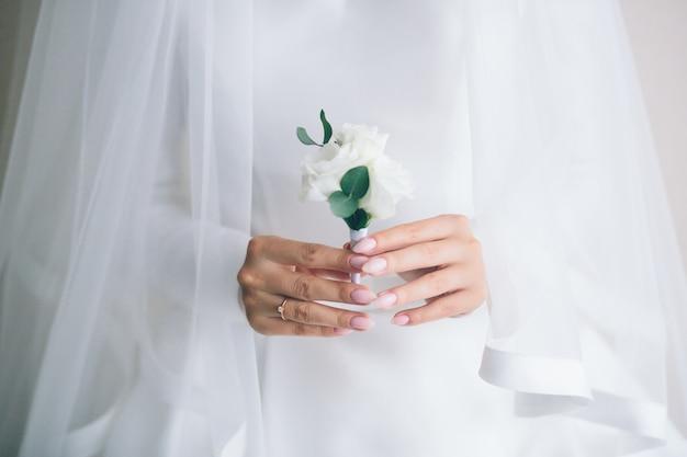 Mani di spose che tengono fiore all'occhiello. donna in un bellissimo abito bianco. preparazioni per le spose. nozze.
