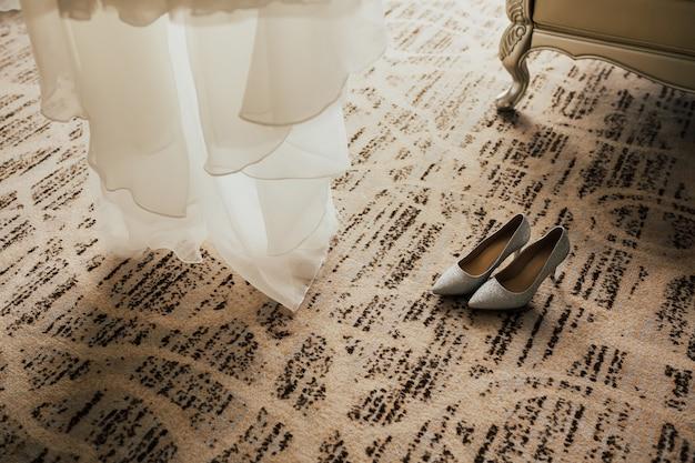 Le scarpe da sposa sono in piedi vicino all'abito da sposa, la mattina della sposa in hotel.