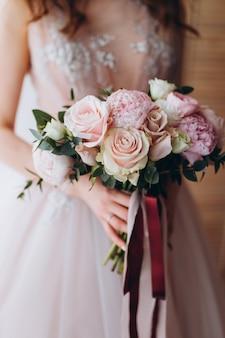 Spose bouquet da sposa con peonie, fresia e altri fiori nelle mani delle donne. colore primaverile chiaro e lilla. mattina in camera