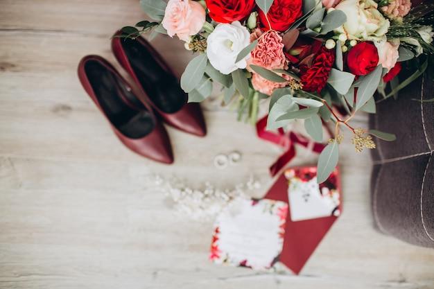 Spose scarpe da sposa con un mazzo di rose e altri fiori sulla poltrona