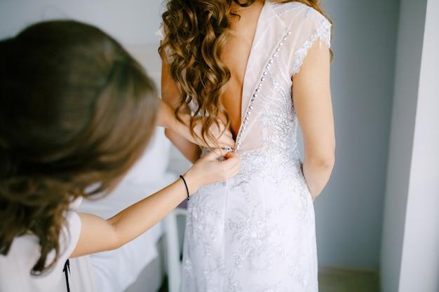 La damigella d'onore aiuta la sposa ad abbottonare l'abito durante i preparativi per il matrimonio