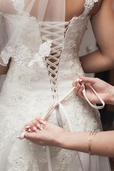 La damigella d'onore sta aiutando la sposa a vestirsi