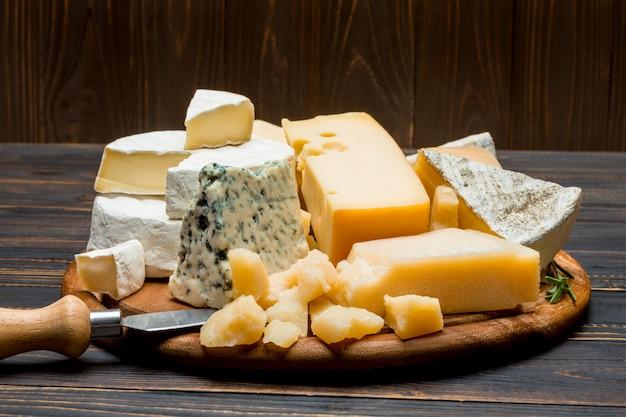 Brie, camembert, roquefort e cheddar su tavola di legno