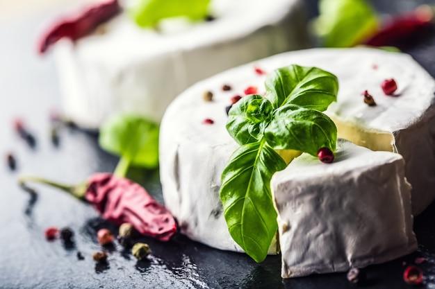 Formaggio brie. formaggio camembert. formaggio brie fresco e una fetta su una tavola di granito con foglie di basilico quattro colori pepe e peperoncino. ingredienti italiani e mediterranei.