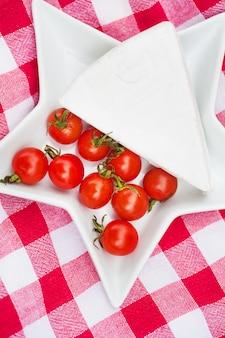 Brie e pomodorini sulla tovaglia rossa. avvicinamento