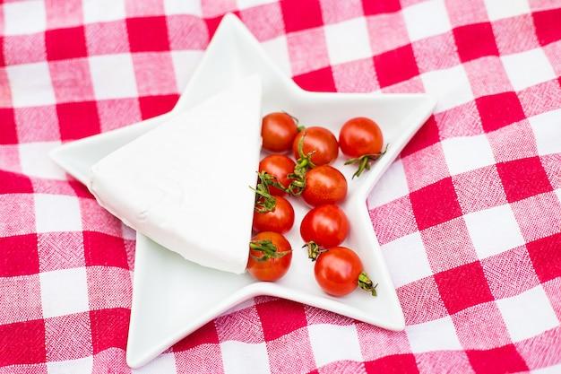 Brie e pomodorini sulla tovaglia rossa