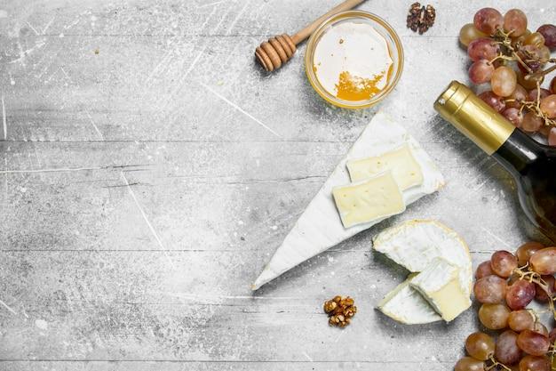 Formaggio brie con miele, uva e vino bianco. su fondo rustico.