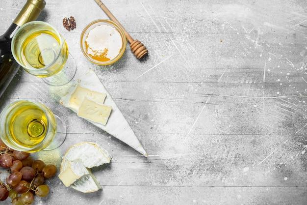 Formaggio brie con miele, uva e vino bianco. su un tavolo rustico.