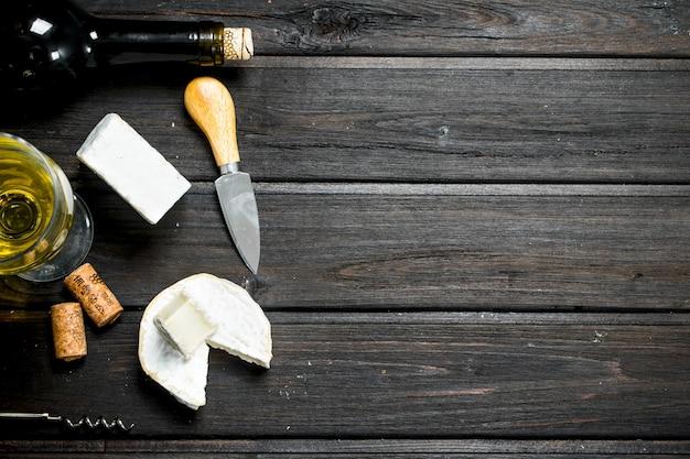 Formaggio brie con vino bianco sulla tavola di legno.