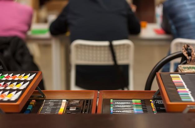 Una valigetta piena di materiale da disegno e da pittura (matite, ombretti, ecc.) con lo sfondo di alcuni scolari sul banco della scuola. Foto Premium