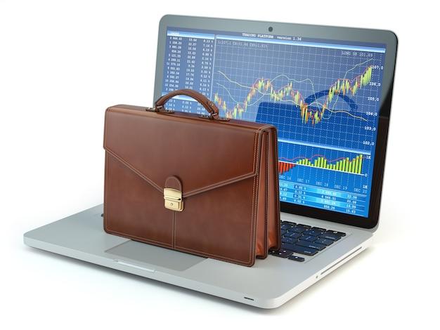 Valigetta sulla tastiera del laptop con grafico del mercato azionario sullo schermo
