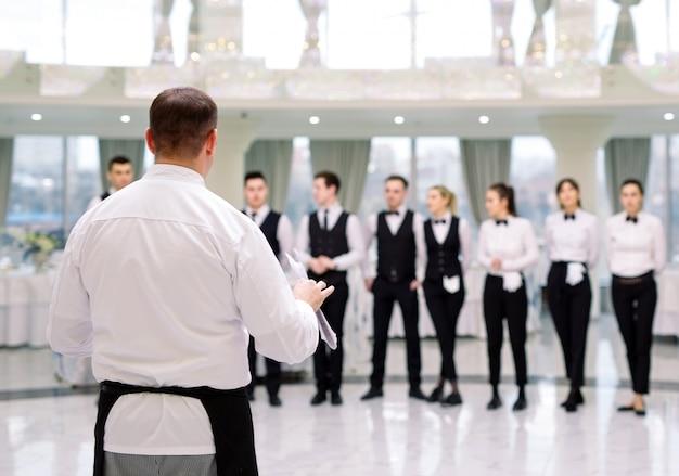 Briefing al ristorante. lo chef sta informando il ristorante .. interagendo con lo chef in cucina commerciale