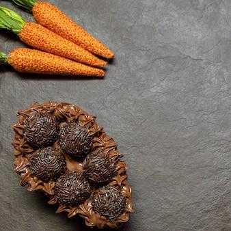 Uovo di pasqua di cioccolato brigadeiro in pietra nera con sfondo con spazio di copia