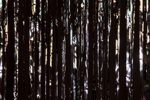 Sfondo luminoso di orpelli in lamina di metallo su parete scura