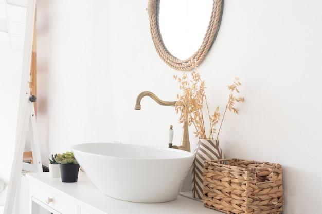 Bagno luminoso, lavandino, miscelatore, specchio, cesto di vimini e fiori su un armadietto bianco.