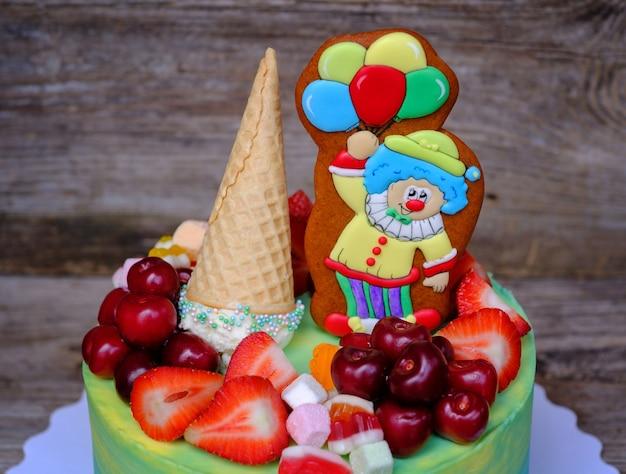 Torta casalinga bella e luminosa con una figura di un allegro pagliaccio, decorata con fragole e ciliegie, con crema blu e gialla
