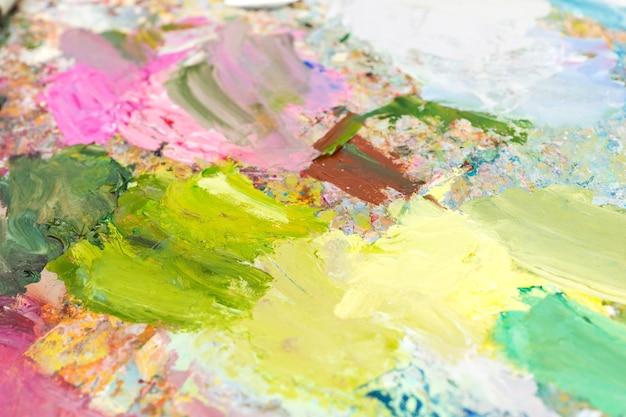 Pittura a olio miscelata brillante su una tavolozza su una tavolozza di un pittore professionista milticolored