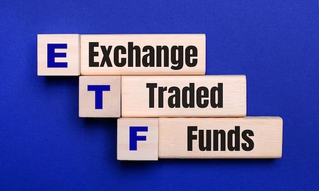 Su uno sfondo blu brillante, blocchi e cubi di legno chiaro con il testo etf exchange traded funds