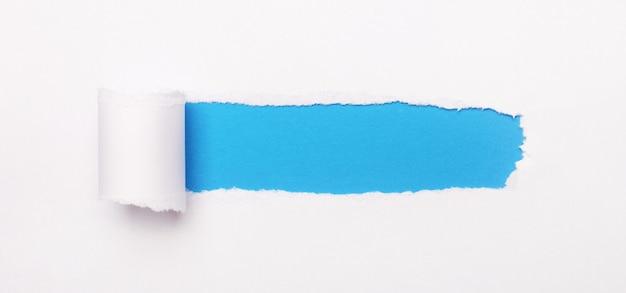 Su uno sfondo blu brillante, carta bianca con una striscia strappata e un posto per inserire il testo. modello