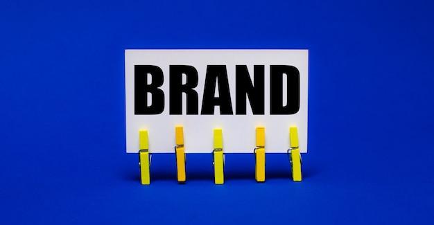 Su uno sfondo blu brillante su mollette gialle, una carta bianca con il testo brand