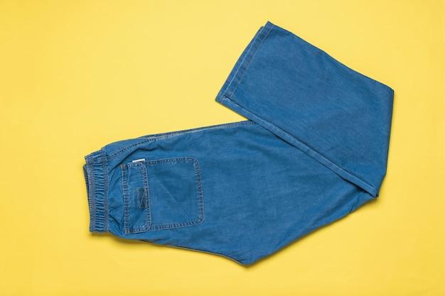 Jeans estivi da uomo blu brillante su una superficie gialla. abbigliamento da uomo in denim alla moda. disposizione piatta. la vista dall'alto.