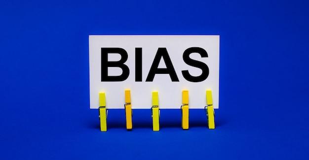 Su una superficie blu brillante su mollette gialle, una carta bianca con il testo bias