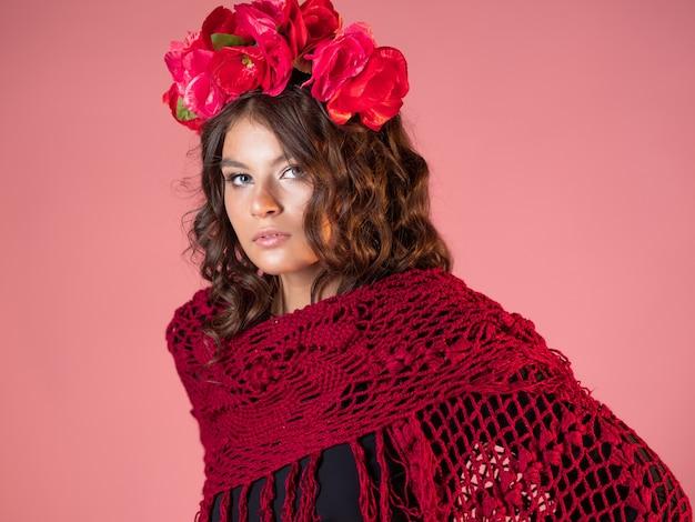 Una giovane donna brillante e audace con rose in testa e un mantello rosso a maglia