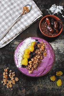 Ciotola per colazione luminosa con frullato di protoni viola e muesli. frullato viola protonico.