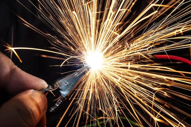 Scintille ardenti luminose volano da contatti chiusi in modo errato. il concetto di pericolo di scosse elettriche e sicurezza.