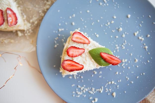 Cheesecake luminosa decorata con fragole fresche e foglie di basilico, tagliata un pezzo su un piatto