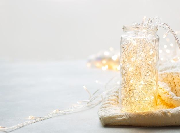 Sfondo di natale luminoso con ghirlanda in vaso di vetro