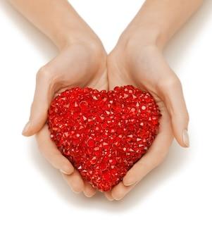 Immagine luminosa del primo piano delle mani della donna che tengono il cuore