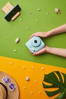 Composizione pop di colore brillante di mani femminili che tengono la fotocamera istantanea su sfondo tropicale grafico con vibrazioni di vacanza,