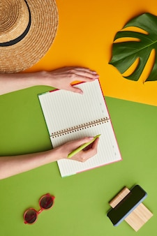 Composizione pop di colore brillante di mani femminili scrivendo nel pianificatore su sfondo tropicale grafico con vibrazioni di vacanza,