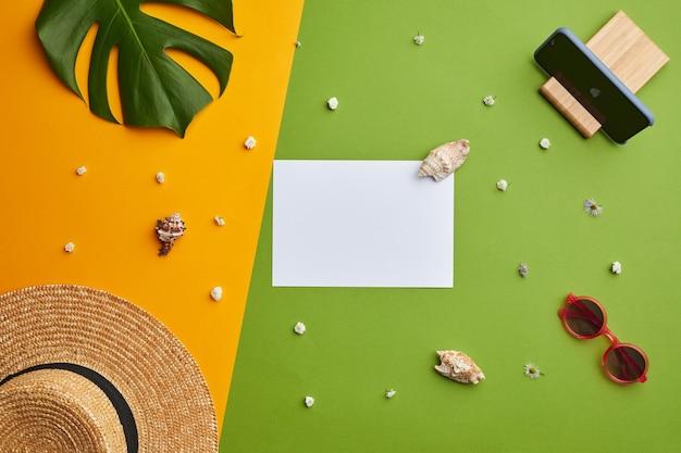 Composizione pop di colore brillante di carta bianca vuota cappello di paglia su sfondo tropicale grafico con vibrazioni di vacanza,