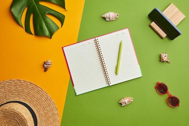Composizione pop di colore brillante di cappello di paglia e pianificatore aperto su sfondo tropicale grafico con vibrazioni di vacanza,