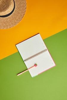 Composizione pop di colore brillante di cappello di paglia e pianificatore aperto su sfondo tropicale grafico,