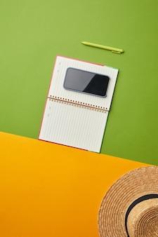 Composizione pop di colore brillante di cappello di paglia, smartphone e pianificatore su sfondo tropicale grafico,